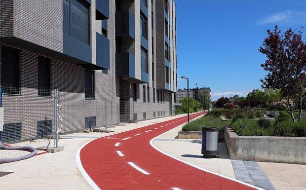 En Camino Casa la Vega se ha pintado una acera bici pegando a los bloques de pisos.